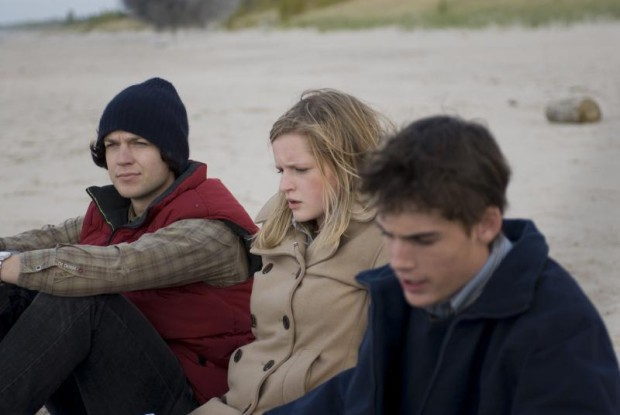 Image du film The Bend de Jennifer Kierans dans laquelle on voit trois jeunes, pensifs, assis sur une plage de sable