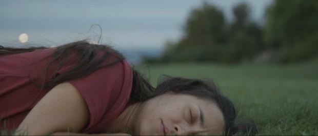 Image de la comédienne Catherine Cédilot allongée dans l'herbe dans une scène du film Toujours encore