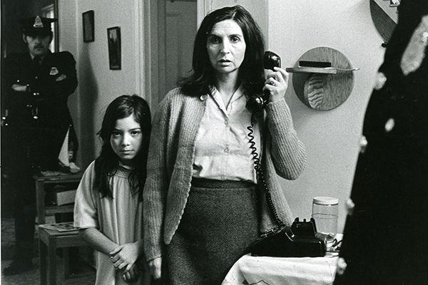 Sur la photo, la comédienne Hélène Loiselle est arrêtée par deux policiers, sa petite fille blottie contre elle dans le film Les Ordres (Collection Cinémathèque québécoise)