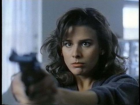 Image de la comédienne Krista Errickson braquant un pistolet droit devant, dans le film Killer Image