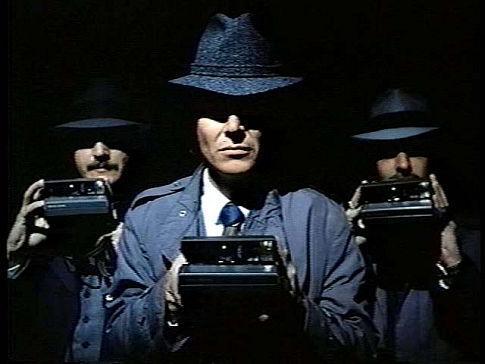 Image extraite du film Killer Image dans laquelle trois hommes en complet noir tiennent un appareil photo à la main