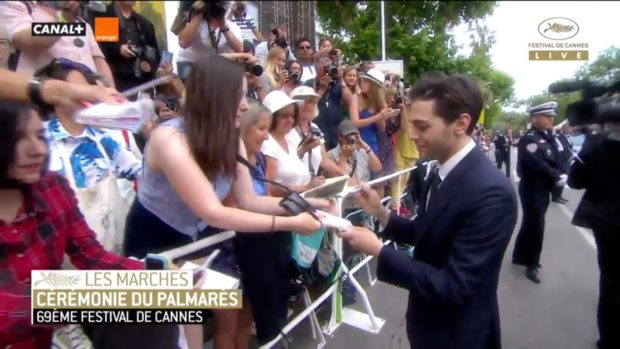 Xavier Dolan signe des autographes avant de monter les marches de Cannes pour la cérémonie de clôture (image-écran de la webdiffusion de Cannes 2016)