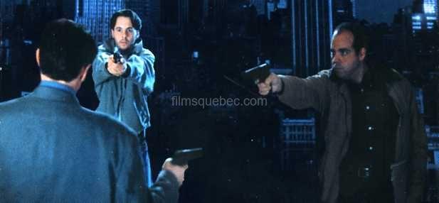 Une scène de Sublet (John Hamilton) - Deux hommes tiennent en joue un quidam avec leurs pistolets