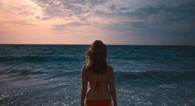 Image extraite du film Isla Blanca - on y voit de dos la comédienne Judith Baribeau en bikini rouge faisant face à la mer