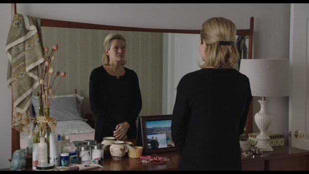 La comédienne québécoise Élise Guilbault jour Monique dans le film Pour vivre ici de Bernard Émond - Sur la photo, elle se tient devant un miroir et semble habitée d'une profonde réflexion.