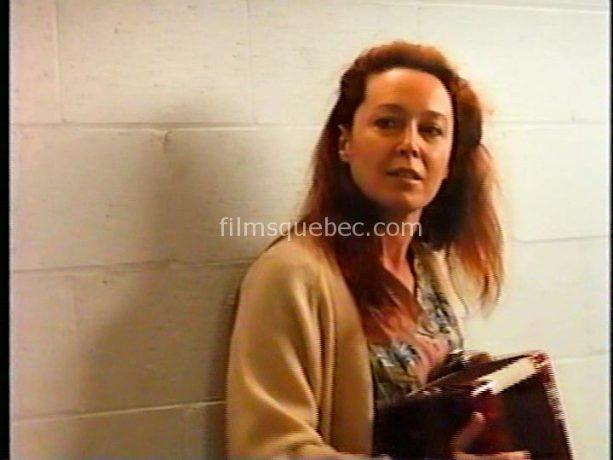 Louise Laprade (l'accordéoniste) dans Pablo qui court de Richard Bergeron (image extraite du film (capture VHS) - Sur la photo, elle se tient le long d'un mur blanc avec son accordéon sur les genoux)