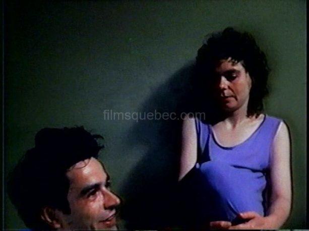 Claude Fortin et Johanne Goulet dans Le voleur de Caméra - Assise dans un lit, elle le regarde de haut. Il est en train de se lamenter sur son sort.
