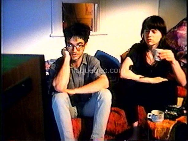 Claude Fortin et Madeleine Bélair dans Le voleur de caméra. Assis côte à côte, ils regardent les nouvelles à la télévision en buvant un café.