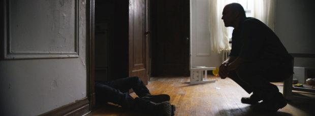 Hugh Thompson dans Touched de Karl R. Hearne (un homme est accroupi devant un placard duquel ressortent les jambes d'une personnes inanimée)