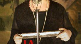 Affiche temporaire du film La Bolduc de François Bouvier on y voit la comédienne tenant un harmonica dans les mains, en face d'un micro.