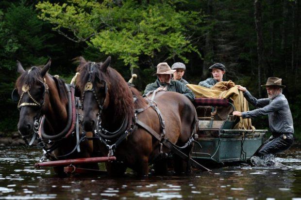 """Image des comédiens Guy Thauvette (g.), Tristan Goyette Plante, Justin Leyrolles-Bouchard, Roy Dupuis (d.) traversant une rivière avec un chariot dans le film """"Pieds nus dans l'aube"""" de Francis Leclerc"""