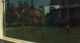 Image tirée de Une colonie de Geneviève Dulude-De Celles (pensive, une feune femme regarde par la fenêtre)