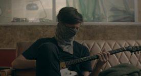 Emmanuel Schwartz dans le film Nous sommes Gold d'Éric Morin (le comédien joue de la guitare sur un divan avec un bandeau lui masquant presque tout le visage)