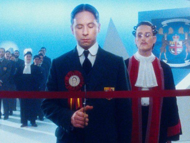 Image extraite du film Twentieth Century de Matthew Rankin (les yeux fermés, un homme coupe un cordon rouge, en signe d'inauguration)