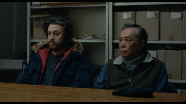 Les acteurs Mikael Gouin et Nguyen Thanh Tri sont accotés à une table en train d'écouter un interlocuteur que l'on ne voit pas (image extraite du film)