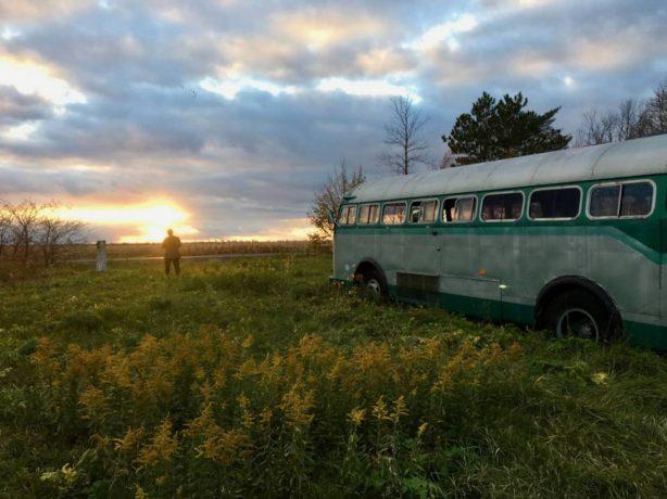 Wilcox et son autobus vert face au soleil couchant dans la campagne québécoise (extrait du film de Denis Côté)