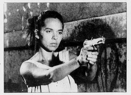 Angela Roa (Eva) dans le film Eva Guerrillera de Jacqueline Levitin (la jeune femme pointe un pistolet face à elle)
