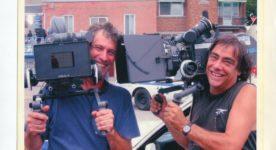Le directeur photo Jean-Pierre St-Louis et le cinéaste Robert Morin sur un plateau de tournage avec leur caméra à l'épaule.