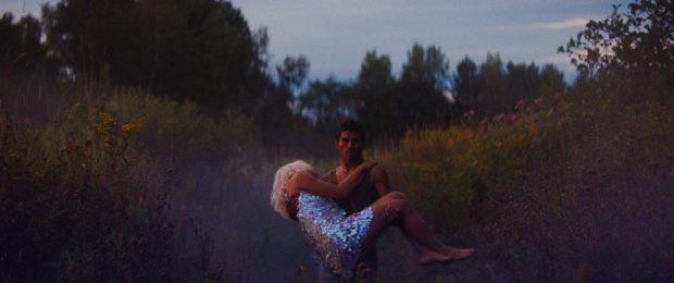 Un homme torse nu porte une jeune femme évanouie dans une clairière. Image extraite du film Les oiseaux ivres, de Ivan Grbovic.